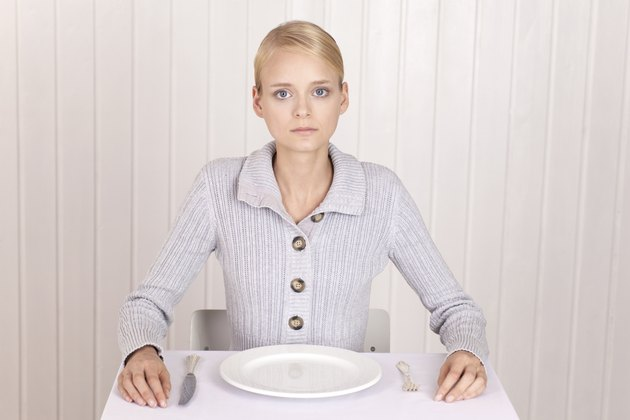 Anorectic woman in front of empty plate