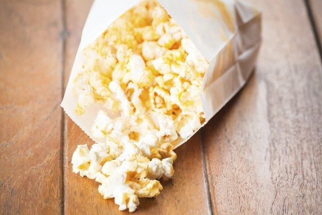 Popcorn paper bag opened with corn spilling out