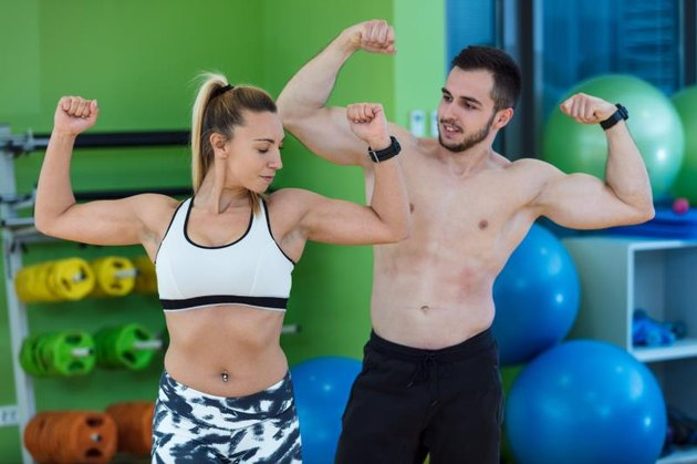 sexy caucasian man and woman in gym couple train in fitness club with weights lifestyle wellness exercising with joy.