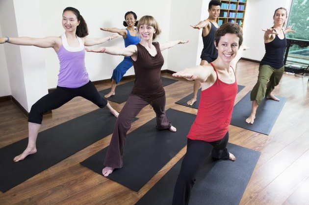 Group of people with arms outstretched doing yoga during a yoga class