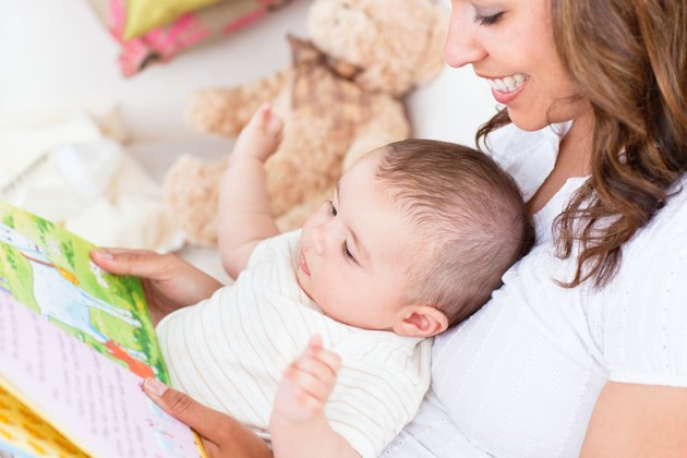 Joyful mother showing images in a book to her cute little son