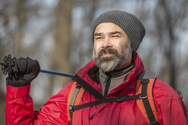 Portrait of hiker man with backpack and trekking pole
