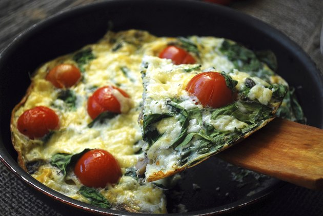 Frittata with cherry tomatoes, cheese and spinach. Close up