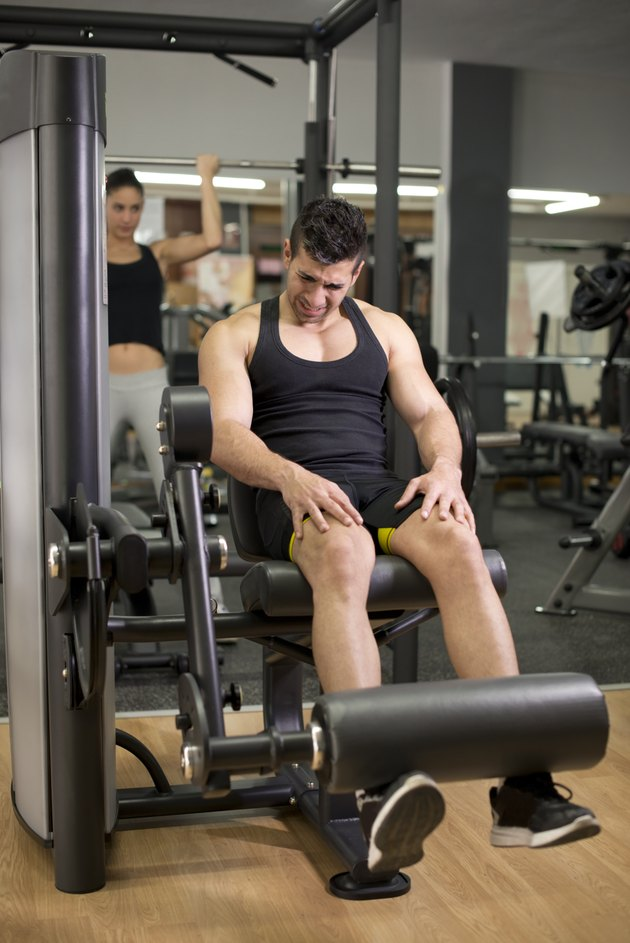 Young man training legs at gym pull machine