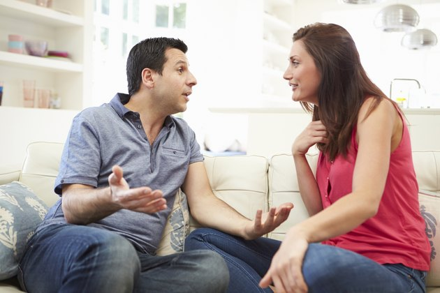 Hispanic Couple Sitting On Sofa Arguing