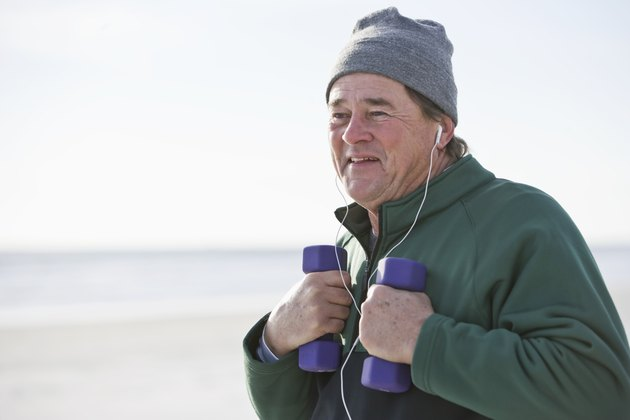 Senior man exercising with hand weights outdoors