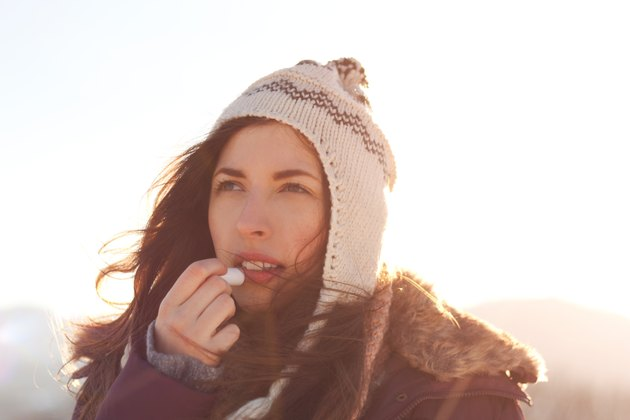 Women outdoor taking care of lips