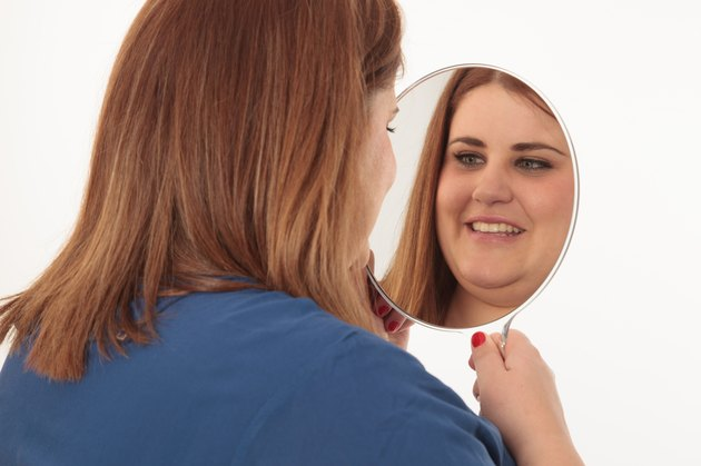 Smiling woman looking herself in a mirror