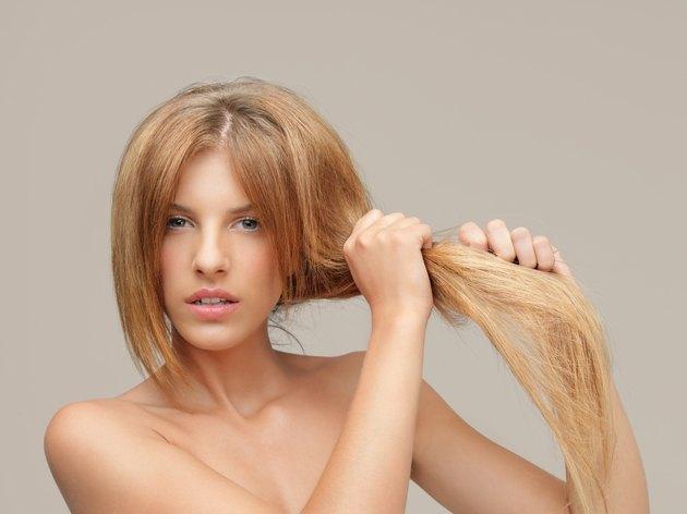 upset woman pulling dry hair split ends
