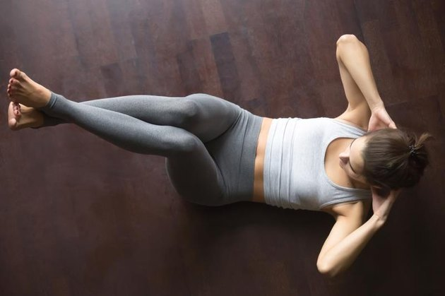 Beautiful young model working out at home, doing fitness exercise on floor, Abdominal Knee Crunches for upper and lower abs, Sit Ups with hands behind the neck. Core training. Top view. Full length