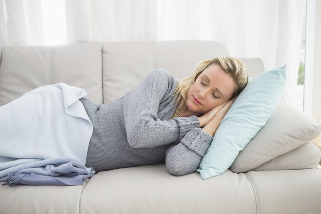 Casual pretty blonde lying on couch sleeping