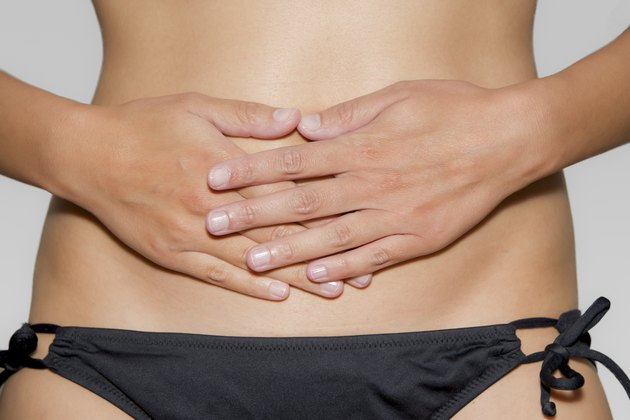 woman has her hands on stomach
