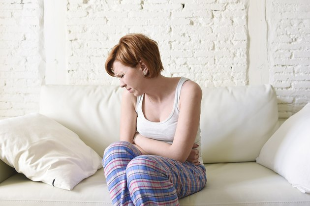 young woman suffering period pain stomach cramp sittingon couch