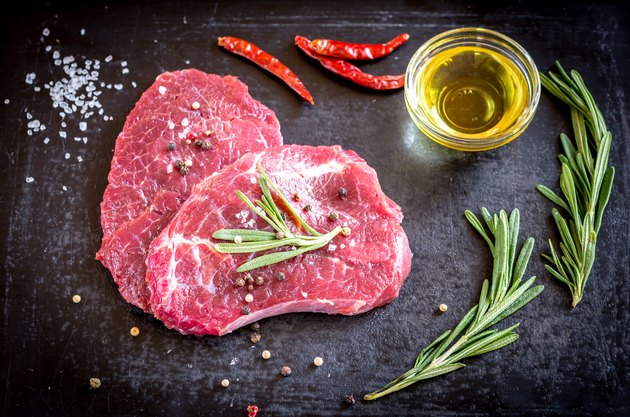 Fresh beef steaks with ingredients on the dark background