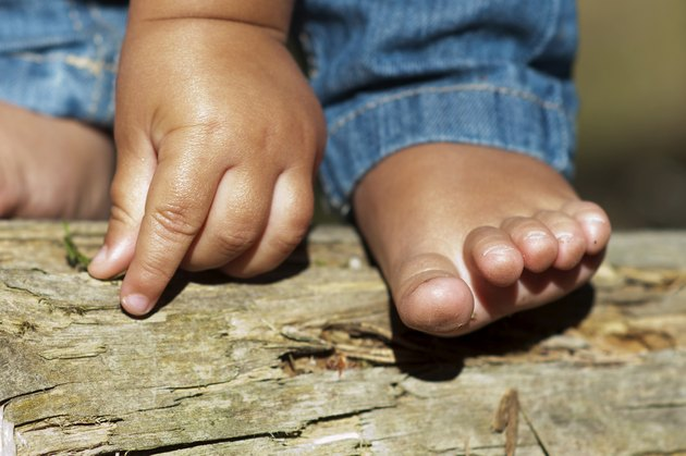 Child hand and foot outdoors