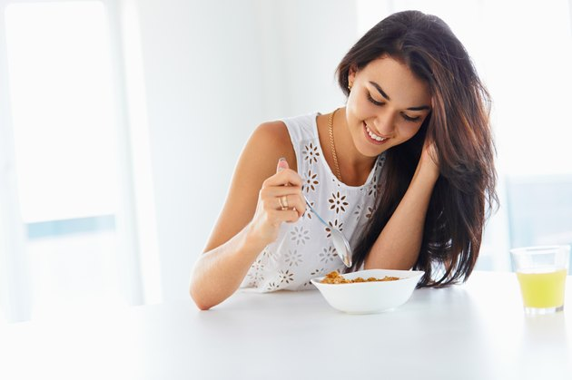Wellness concept. Woman eating cereal and smiling. Healthy break