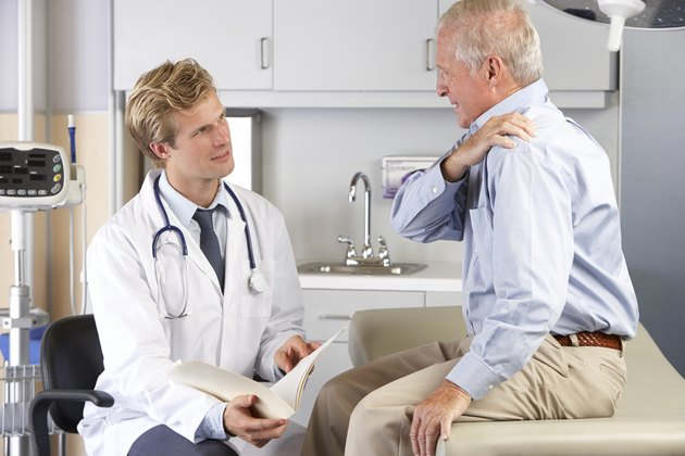Doctor Examining Male Patient With Shoulder Pain