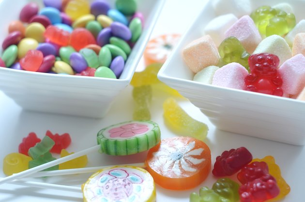 Two bowls of colored smarties and sour candies
