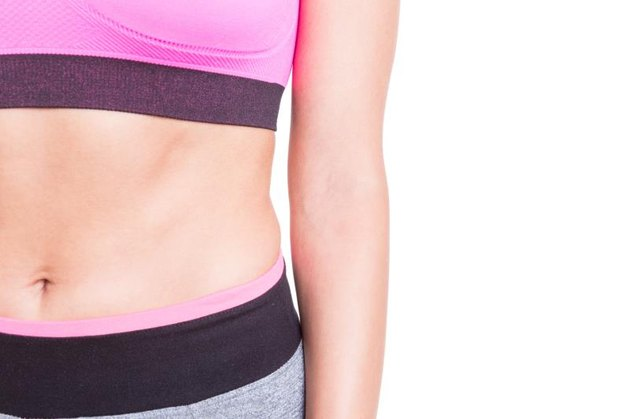 Close-up of sporty abs of woman wearing bustier isolated on white background with copy text space