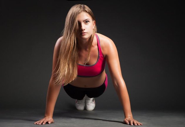 Young girl in sport outfit making push-up on hands and looking at camera on plain black background.