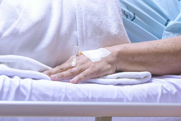 the old man patient  in hospital with tubes in hand