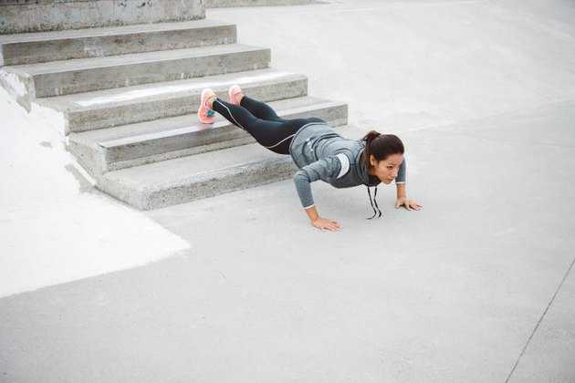Urban fitness woman workout doing feet elevated push ups and exercising outdoor. Motivated female athlete training hard.