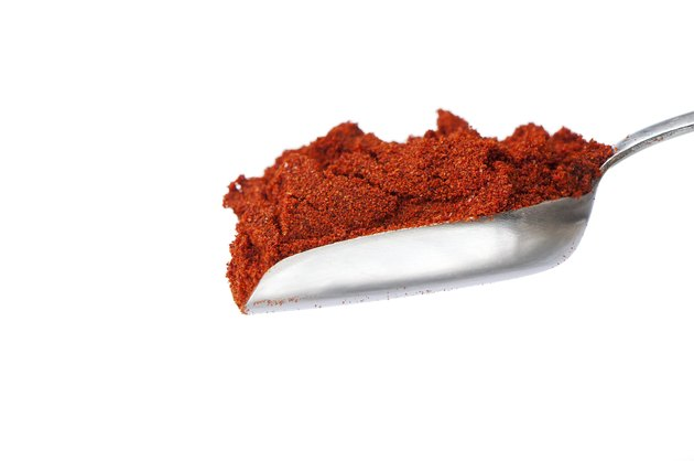 silver spoon with red paprika powder on white background