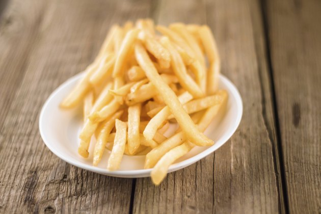 fries on white dish at wooden table