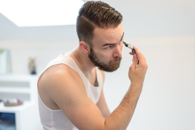 Young man shaving above his beard
