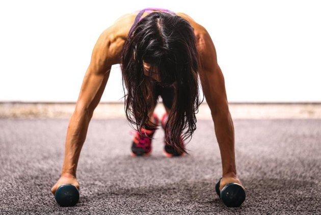 A fit woman work uses dumbbells to enhance her push-up.