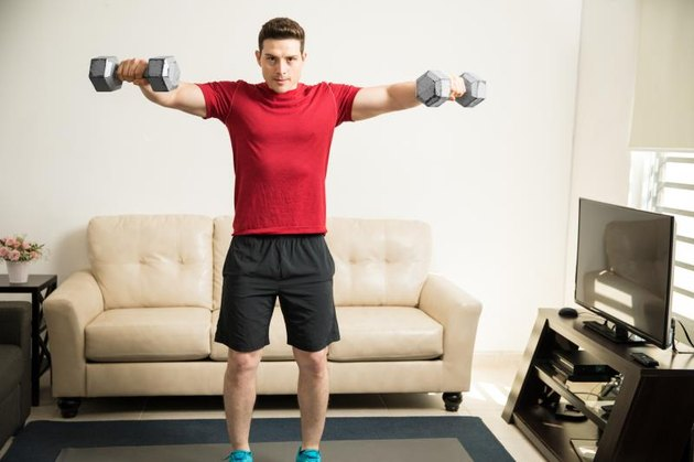 Athletic Hispanic young man exercising his shoulders and doing side raises with a pair of dumbbells at home