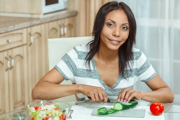 Beautiful woman slicing cucumber for salad in modern kitchen