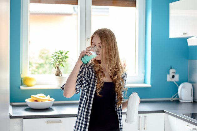 Thirsty young blond woman drinking milk