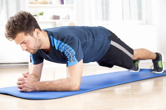 Full Length Shot of a Fit Young Man Performing Planking Exercise on a Mat While Facing the Floor.