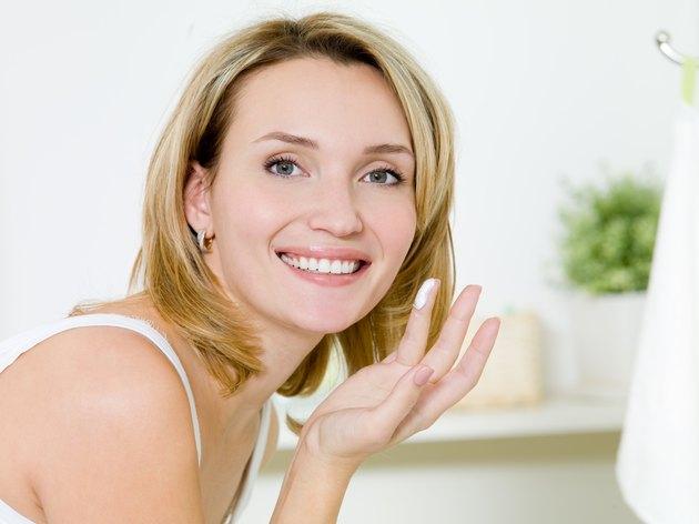 girl applying moisturizer  cream on face