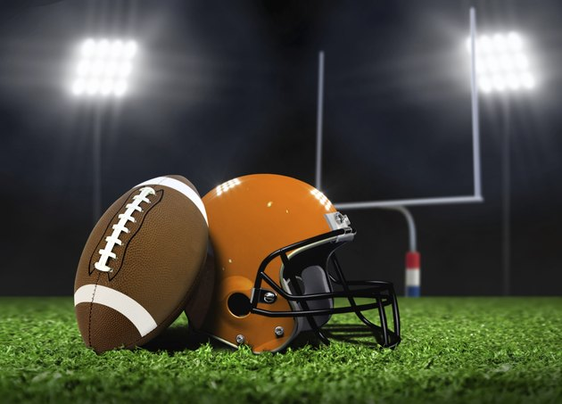 Football Ball and Helmet On Grass under Spotlights