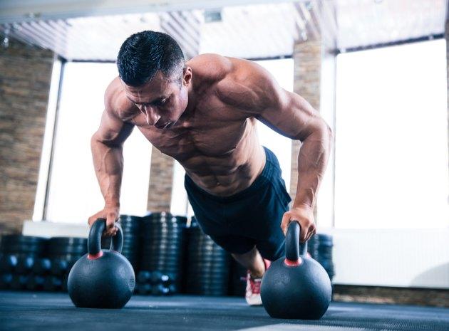 Muscular man doing push ups in gym