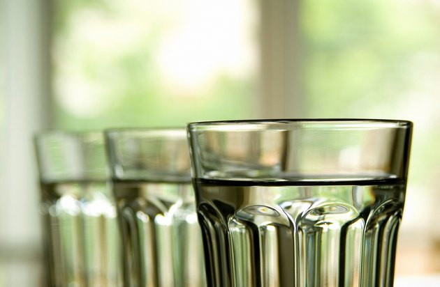 Three full clear glasses lined up with drinking water.