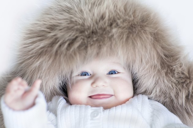Funny baby girl with blue eyes wearing huge winter hat