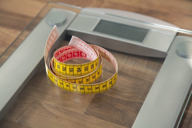Measuring tape on bathroom scale.