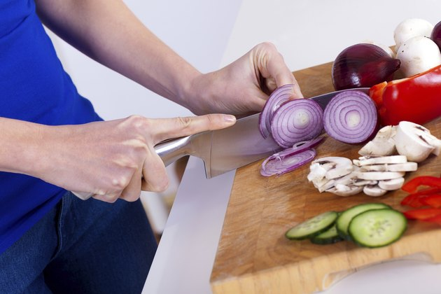 female hands chopping vegetables on a wooden board