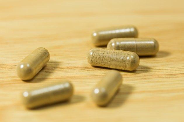 Herbal medicine pills on wood board.