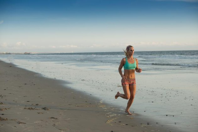 Young woman runs on beach at sunset