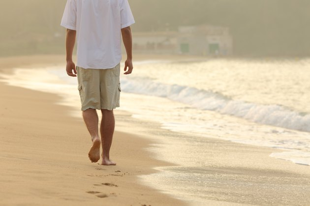 Man walking and leaving footprints on the sand of beach