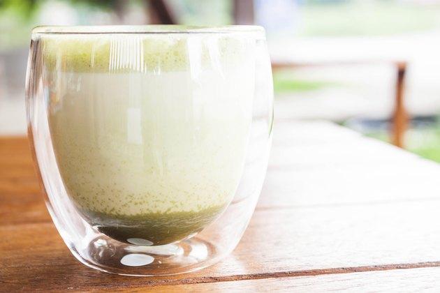 Glass of hot matcha green tea latte at coffee shop