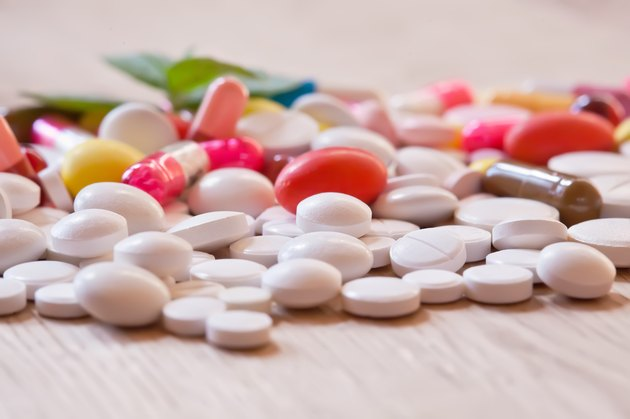 Pills and capsules on the wooden background