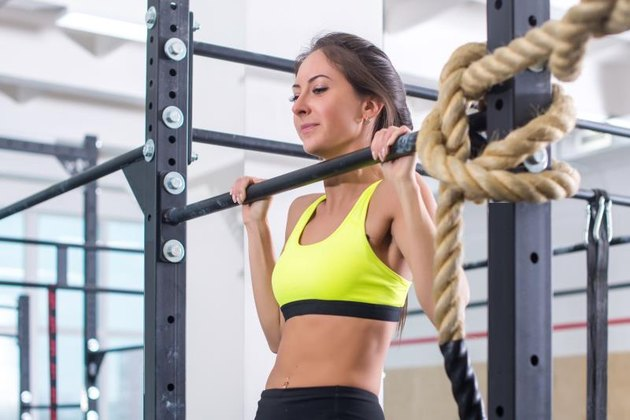 Athlete fit woman performing pull ups in a bar exercising at gym