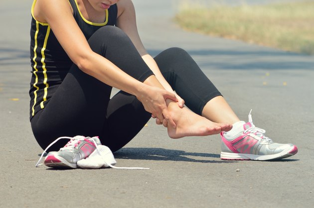 Young woman suffering from an ankle injury while exercising and