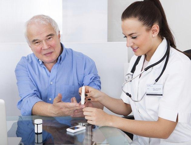 Doctor Using Lancelet On Senior Man