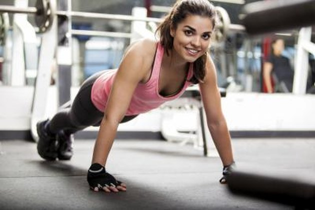 Happy young Hispanic woman doing some push ups and working out at the gym